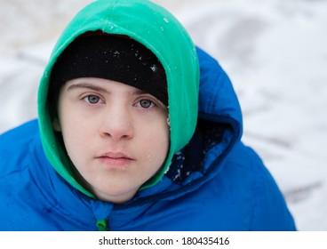 horizontal orientation close up of a boy with autism and down's syndrome dressed in a colorful hat, sweatshirt and jacket, with snowy background / Helping the child with Autism Dress Appropriately