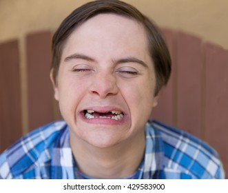 horizontal orientation close up color image of a teenage boy with Autism and Down's Syndrome making a silly face with his eyes closed / Happy Boy with Autism and Down's Syndrome Smiles with Eyes shut