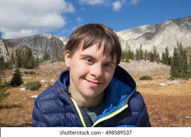 horizontal orientation close up of a happy, smiling, teenage boy with autism and down's syndrome in the foreground, and majestic mountain scenery in the background /Happy Teenage Boy Hiking