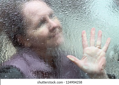 horizontal orientation close up outline of a smiling woman and her hand through a window covered in thick ice / Hope through the Winter
