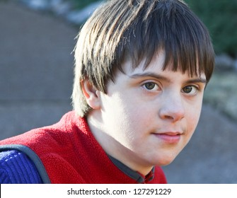 horizontal orientation close up portrait of smiling boy with autism and down's syndrome in outdoor setting / Dual Diagnosis