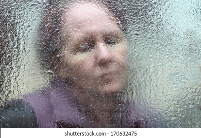 horizontal orientation close up of a sad looking woman behind a glass window which is covered in thick ice / The Long, Cold Winter of the Elderly