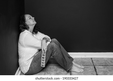 horizontal orientation close up, in black and white, of a single woman sitting in a corner with a pill box in one hand, looking exhausted / Finding the Right Medication