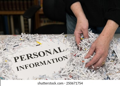 horizontal orientation close up of a woman's hands gathering shredded paper to recycle with the words PERSONAL INFORMATION shown / Protecting Personal Information