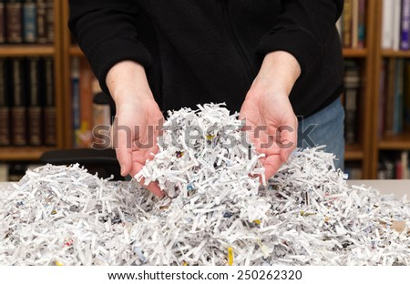 horizontal orientation close up of a woman's hands holding shredded paper in an office environment /  Hands Full of Shredded Documents