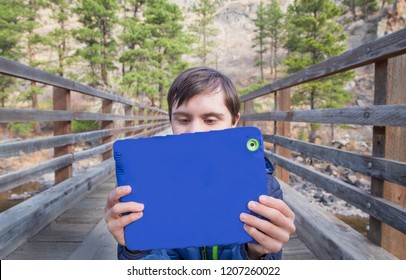 horizontal orientation color image of an attractive teenage boy with autism and down's syndrome on a bridge outside, using his tablet device