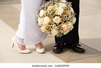 Horizontal orientation color image of a bride and groom's feet and bridal bouquet outside on a sunny day.