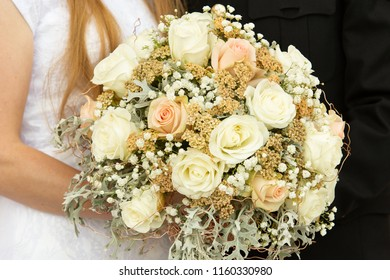 Horizontal orientation color image of a bride and groom (torso only) holding a bridal bouquet of pale shades of yellow, pink and green