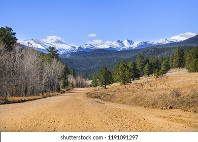 horizontal orientation color image of a dirt road leading to snow capped mountains in Spring in Colorado, USA
