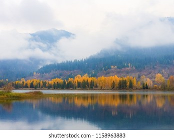 Horizontal orientation color image of fall colors reflected in water and low lying clouds in Noxon, Montana, USA