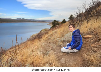 horizontal orientation color image of a happy teenage boy with autism and Down's Syndrome outside with his tablet / Teenage Boy with Autism and Down's Syndrome with tablet device at Carter Lake, CO