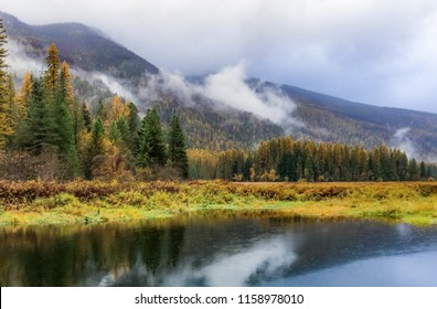 Horizontal orientation color image of low lying clouds, mountains and their reflection in water in Montana, USA
