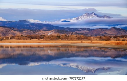 Horizontal orientation color image of McIntosh Lake, Longmont, Colorado, USA at sunrise, with Meeker and Long's Peak in the background.