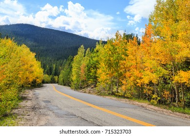 horizontal orientation color image of an old highway with beautiful Aspen trees and fall colors, with mountains in the background / Colorado in Autumn