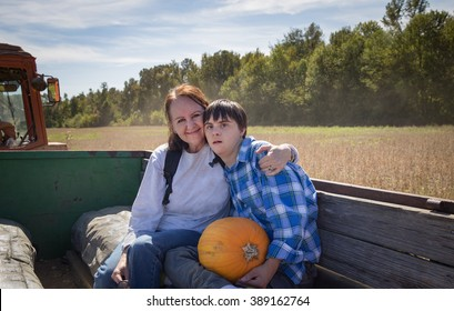 horizontal orientation color image with shallow depth of field, with a happy mother and her son with autism and down's syndrome on a hay ride / Choosing a pumpkin with Mom