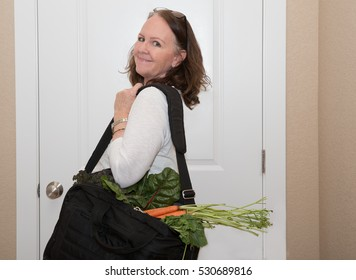horizontal orientation color image of a single, happy woman in business attire with a  briefcase full of fresh veggies / Maintaining Nutrition on the Road