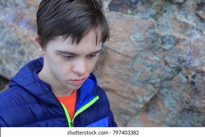 Horizontal orientation color image of a teenage boy with autism and Down's Syndrome in the foreground, and a rocky wall in the background