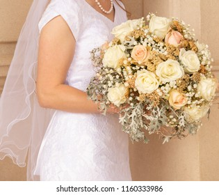 Horizontal orientation color image of the torso of a bride in a white gown, holding a bridal bouquet of pale pink, yellow and green blossoms.