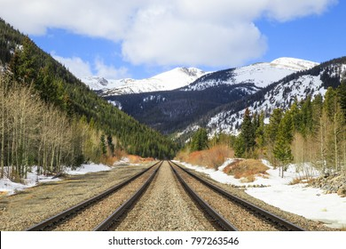 Horizontal orientation color image of two sets of train tracks leading into Rollins Pass, Colorado, USA in winter