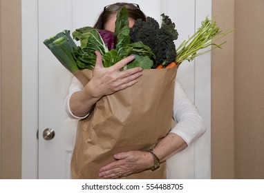 horizontal orientation color image of a woman holding a paper bag overflowing with vegetables / Adding Veggies to your Diet