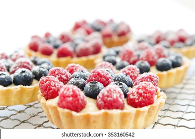 Horizontal orientation of a cooling tray of tarts topped with raspberries and blueberries, sprinkled with icing sugar