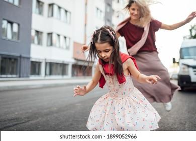 Horizontal outdoor image of a happy little girl playing hopscotch with her mother on playground outdoors. Child plays with her mom oustside. Kid plays hopscotch drawn on pavement. Activities and games