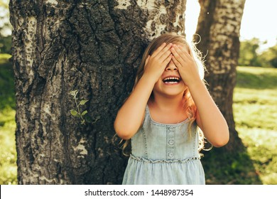 Horizontal outdoor image of smiling little girl covering her eyes with both hands, playing hide and seek standing next a big tree. Adorable child having fun outdoors in the park. Childhood