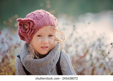 Horizontal outdoor portrait of beautiful child girl in pink knitted hat looking out of camera with water on background