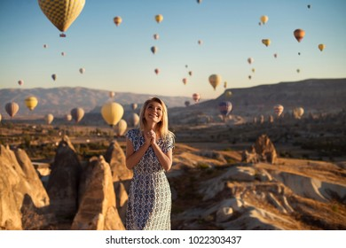 Horizontal outdoor shot of happy blonde young smiling woman in dress being excited as stands on high mountain looks upwards and sees many parachutes flying in air, admires beautiful view on hill.
