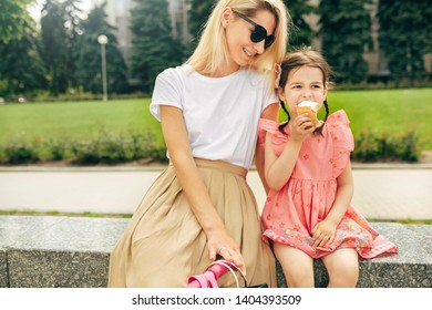 Horizontal outdoors image of happy cute little girl sitting with mother on the city street and eating ice-cream. Fun girl kid and mom having fun and playing outside. Motherhood and childhood concept