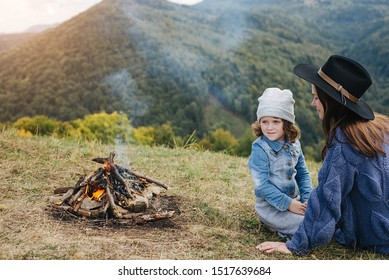 Horizontal outdoors image of young mother and her pretty daughter sitting near to campfire in mountains. Travel, people and healthy lifestyle concept. Caucasian female with baby at mountains