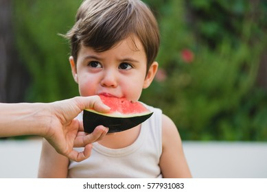 Horizontal outdoors shot of a hand giving to a child the watermelon to taste.
