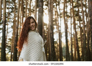 Horizontal outdoors shot of smiling female in the sunny woods looking at camera.