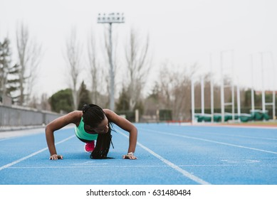 Horizontal outdoors shot of a young black woman doing push-ups on a stadium.