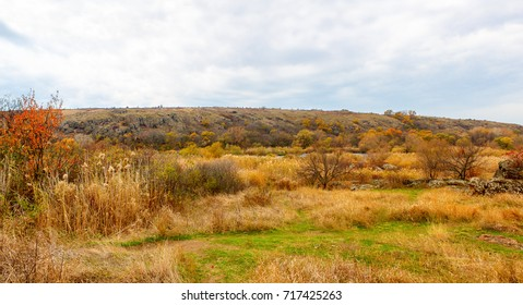 A horizontal panorama of the autumn landscape of the yellowed grass of granite stones, river and yellowed foliage on trees