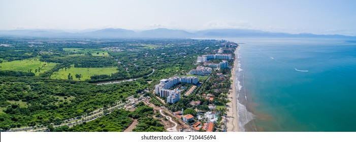 A horizontal, panoramic picture featuring Nuevo Vallarta, Mexico. This picture may feature the beautiful beach and shoreline along its famous hotel row that many travel to throughout the year.