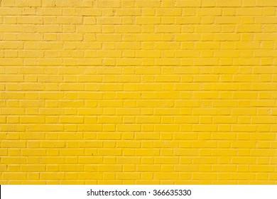 horizontal part of bright yellow painted brick wall