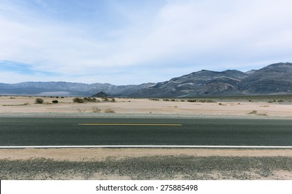 Horizontal Paved Road In Desert With Striped Mountains On Background