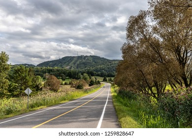 Horizontal of a paved road leading to a green, tree covered ski hill in Bromont, Quebec, on a sunny day
