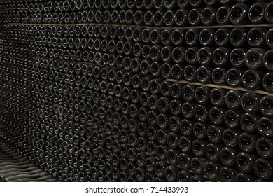 Horizontal perspective view of rows of many champagne bottles in a wine cellar