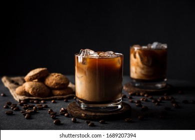 A horizontal photo of 2 rocks glasses with cold iced coffee with milk, coffee beans around, cookies, dark background, deep shadows