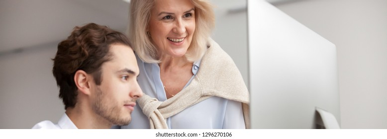 Horizontal photo aged businesswoman mentor looking at pc screen teach help intern colleague, employee having good online work results concept, banner for website header design with copy space for text