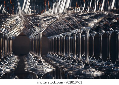 Horizontal photo of aligned empty wine glasses, close up, black and white. Selective focus.