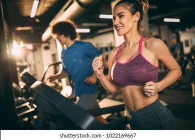 Horizontal photo of attractive woman jogging on treadmill at health club.