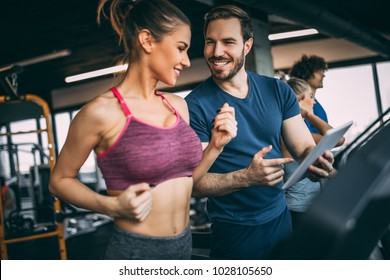 Horizontal photo of attractive woman jogging on treadmill at health club. Training with fitness instructor.