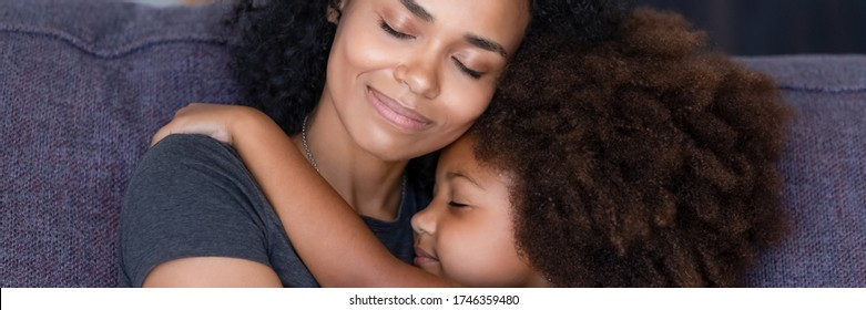 Horizontal photo banner for website header design close up african mom hug little daughter sit on sofa enjoy moment of sweet embracing showing love care, parental protection, motherhood, unity concept