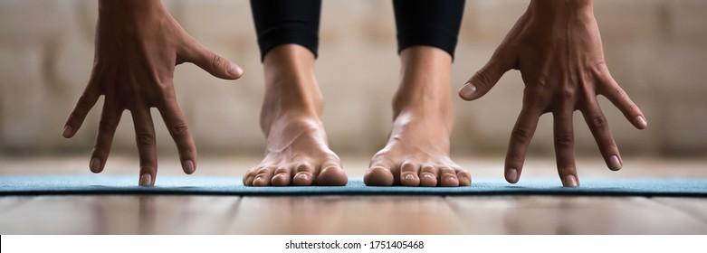 Horizontal photo banner for website header design sportive woman performing forward bend practising yoga uttanasana asana pose. Barefoot legs in pants on yogic mat palms close up view wellness concept