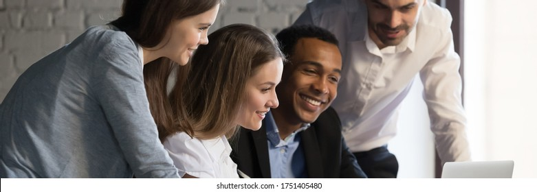 Horizontal photo banner for website header design, diverse employees gathered in office having fun watching funny video, discussing new ideas, brainstorming using laptop enjoy break in workday concept - Shutterstock ID 1751405480