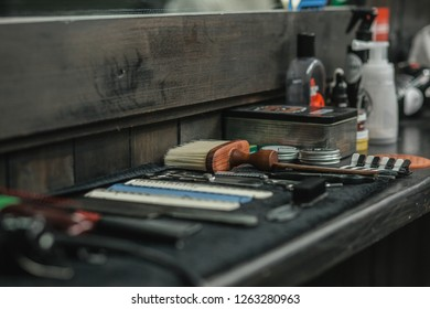 Horizontal photo of barber equipment with brushes and combs on the towel