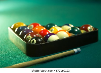 Horizontal photo of a billiard table with the billiard balls arranged in triangle with billiard stick